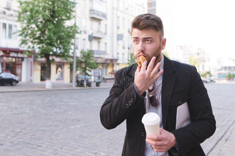 De bezige mens met een kop van koffie en een sandwich in zijn handen moet in zeven haasten werken stock afbeelding