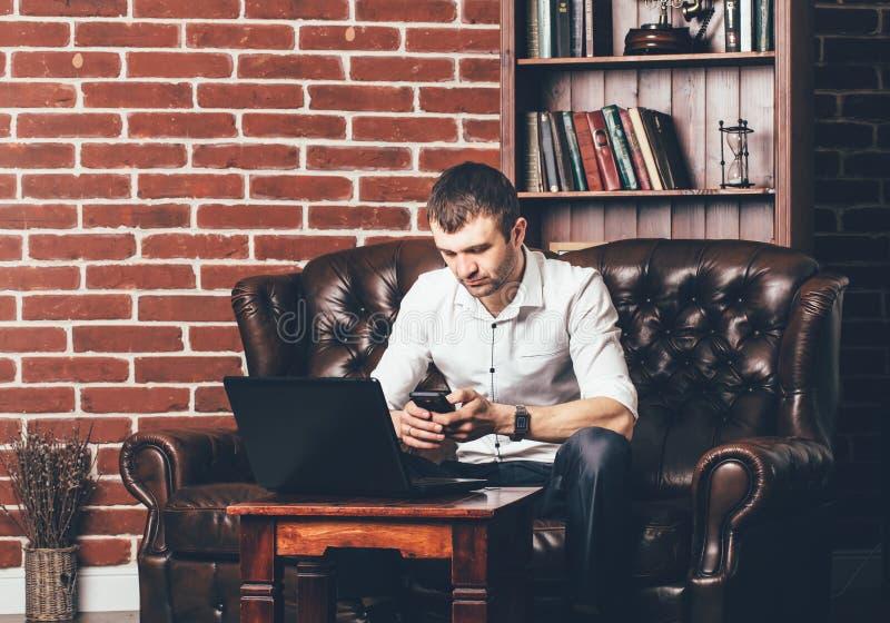 De bezige mens roept een telefoonaantal De zakenman is in zijn kabinet achter zijn laptop op de achtergrond van muur met decorati stock afbeeldingen