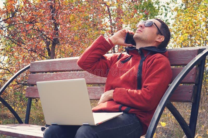 De bezige persoon werkt online buitenbureau aan vakantie jonge mens die aan laptop computer in vrijetijdskleding werken het sprek royalty-vrije stock afbeelding