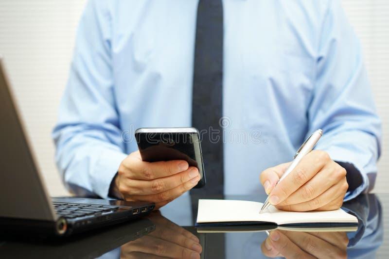 De bezige zakenman bij bureau gebruikt slimme mobiele telefoon, wr stock foto