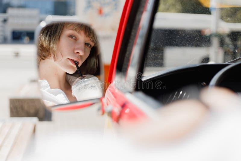 De bezinning in de minivan spiegel van de jonge vrouw in een strohoed kleedde zich in wit overhemd drinkend een milkshake stock foto