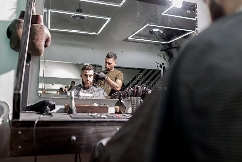 De bezinning in de spiegel van de brutale mens zit als voorzitter en de kapper scheert zijn haren stock afbeelding