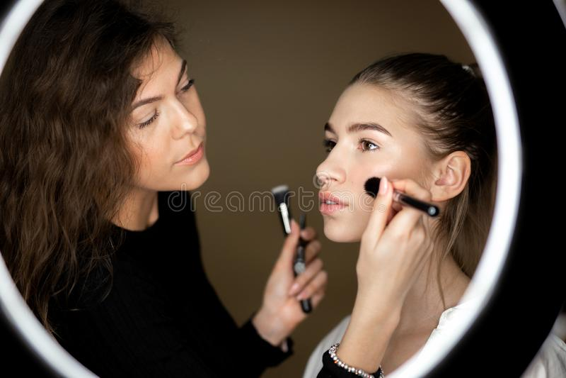 De bezinning in de spiegel van make-upkunstenaar het charmante meisje doet make-up aan een mooi jong meisje stock foto's
