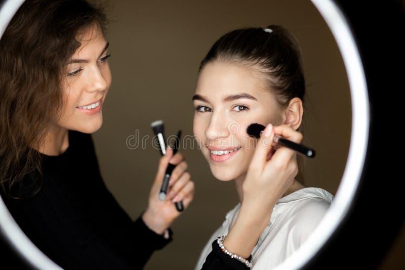 De bezinning in de spiegel van make-upkunstenaar het charmante meisje doet make-up aan een mooi jong meisje royalty-vrije stock foto's