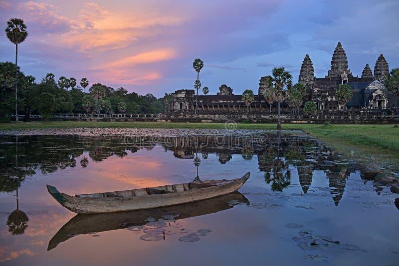 De bezinning van Angkorwat in lotusbloemvijver met boot op zonsondergang, schemering, Siem oogst, Kambodja stock fotografie