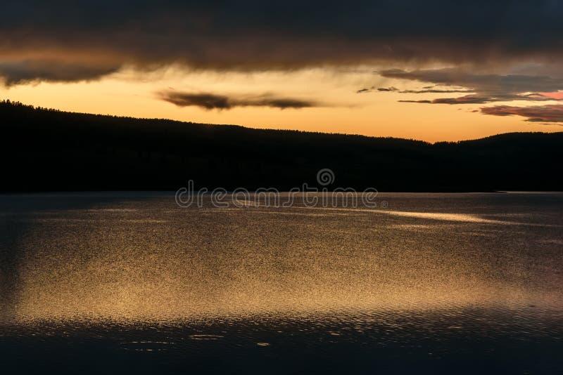 De bezinning van de bergenwolken van het zonsondergangmeer stock afbeelding