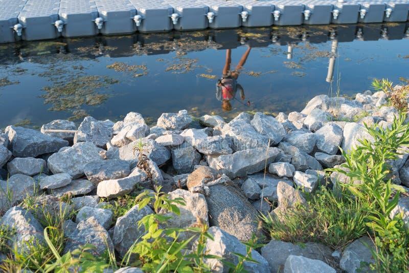 De bezinning van het meisje over het Meer met rotsen op de voorgrond royalty-vrije stock afbeeldingen