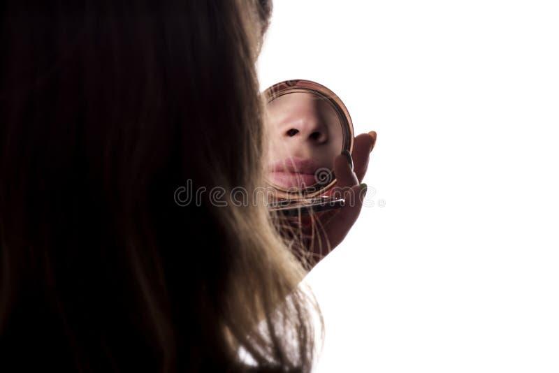 De bezinning van jong mooi wijfje op wit isoleerde backgroundr, vrouwengezicht kijkend in een zakspiegel, het concept de galant stock afbeelding