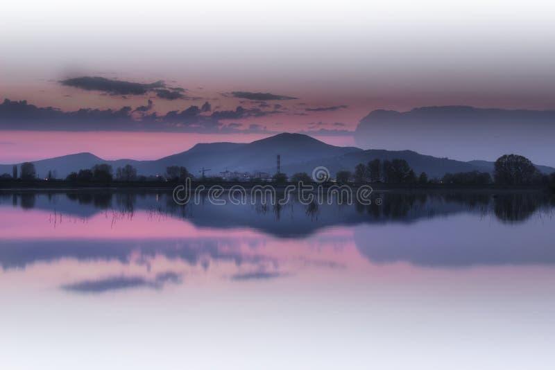 De bezinning van de meerspiegel en purpere zonsonderganghemel stock foto