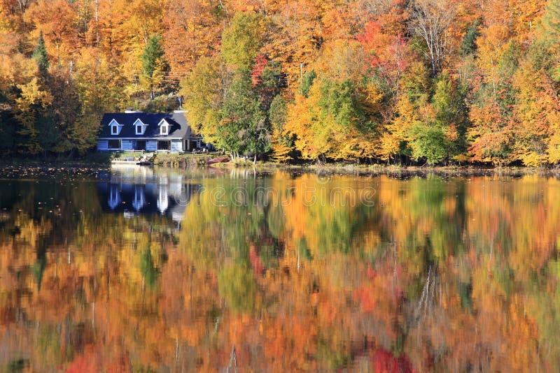 De bezinningen van de herfstkleuren over het meer, Quebec stock fotografie