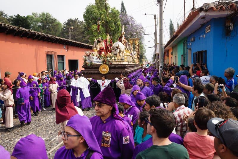 De bezoekers die op purple letten robed mensen die een vlotter met Christus en een kruis dragen bij de optocht van San Bartolome  royalty-vrije stock afbeelding