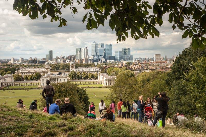 De bezoekers genieten van de mening van de Canary Wharf-wolkenkrabbers van het park van Greenwich in Londen stock afbeelding