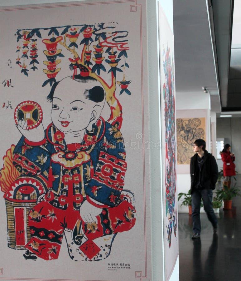 De bezoekers kijken schilderijen van het Nieuwjaar van China de traditionele op een tentoonstelling in de Nationale Bibliotheek va stock foto's