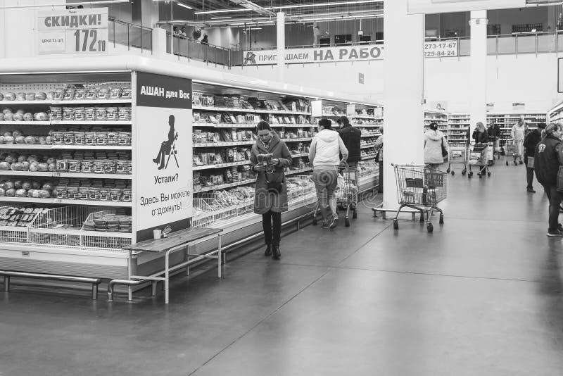 De bezoekers maken aankopen in de supermarkt Auchan in Krasnodar, zwart-witte foto stock fotografie