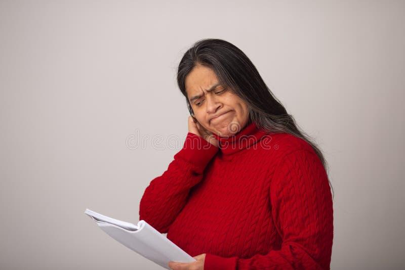 De bezorgde Spaanse Vrouw kijkt door Nota's royalty-vrije stock foto