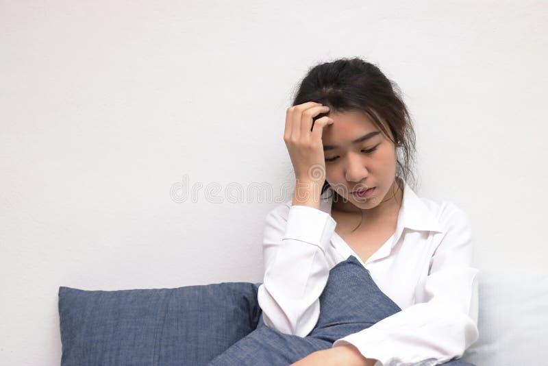 De bezorgdheid drukte jonge Aziatische vrouw met handen op voorhoofd in die aan probleem lijden stock foto's