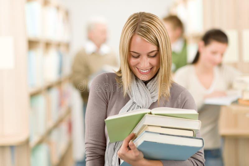 De bibliotheek van de middelbare school - gelukkige student met boek stock afbeeldingen