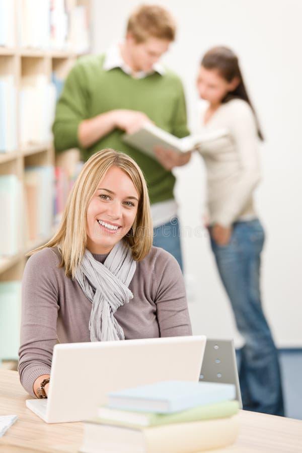 De bibliotheek van de middelbare school - gelukkige student met laptop royalty-vrije stock afbeeldingen