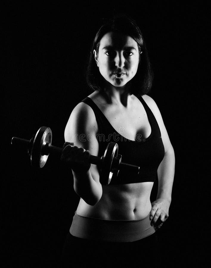 De bicepsen van de geschiktheidsvrouw het krullen stock foto's