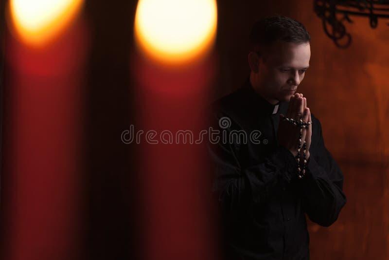 De biddende priester Portrait van priester naast de kaarsen bidt stock foto