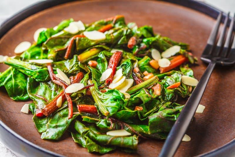 De biet maakt salade met noten in zwarte plaat groen Het gezonde concept van het veganistvoedsel stock foto