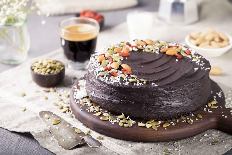 De bietencake van de veganistchocolade met avocado die, verfraaide noten, zaden berijpen stock foto's