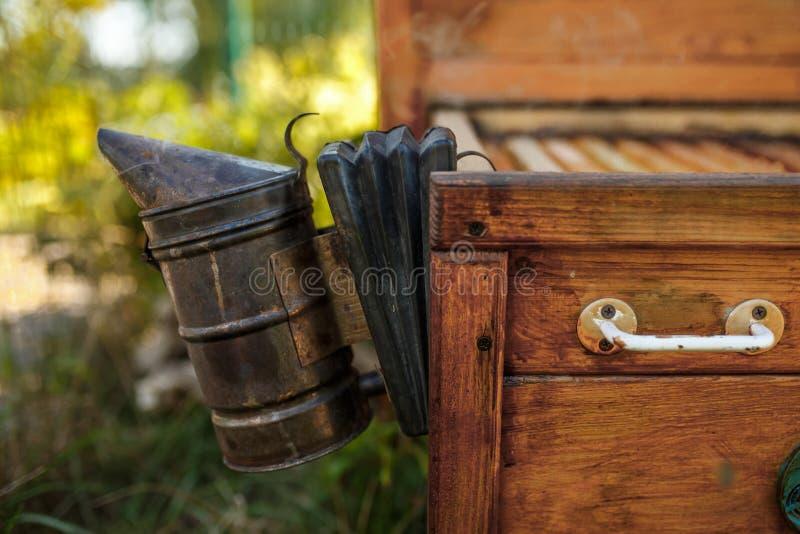 De bijenroker installeerde op houten behive Technologie van beroking van bijen Bedwelmende rook voor veilige honingsproductie stock afbeeldingen