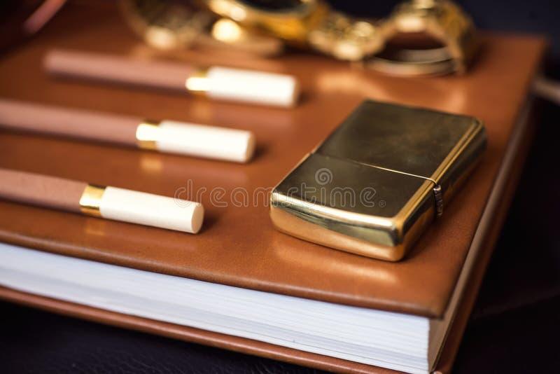 De bijkomende, gouden aansteker van mensen, horloge en sigaretten op de leeragenda royalty-vrije stock foto