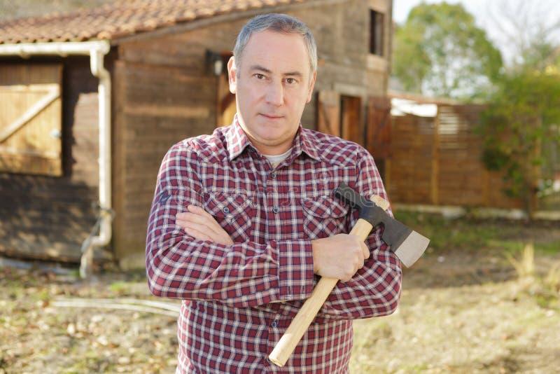 De bijl van de mensenholding voor het hakken van brandhout in werf stock afbeelding