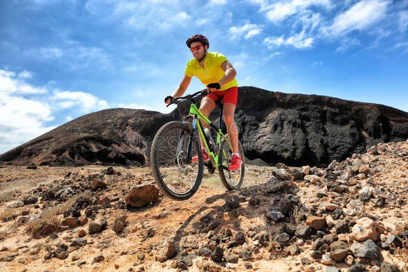 De biking mens die van de bergfiets MTB in de weg rennen die van de sleeprotsen van de bergwoestijn in de lucht berijdende fiets  stock foto's