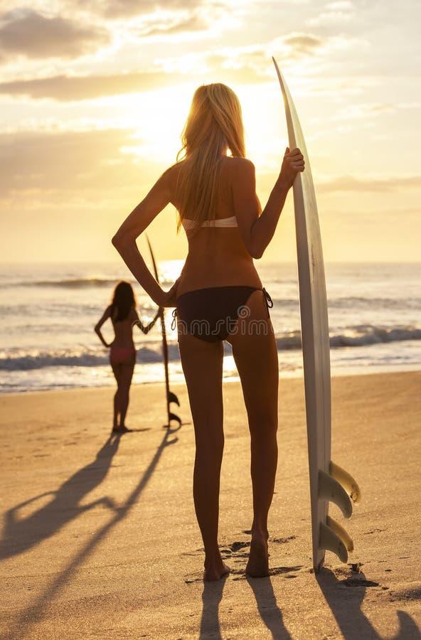 De Bikini Surfer van de vrouw & het Strand van de Zonsondergang van de Surfplank royalty-vrije stock fotografie