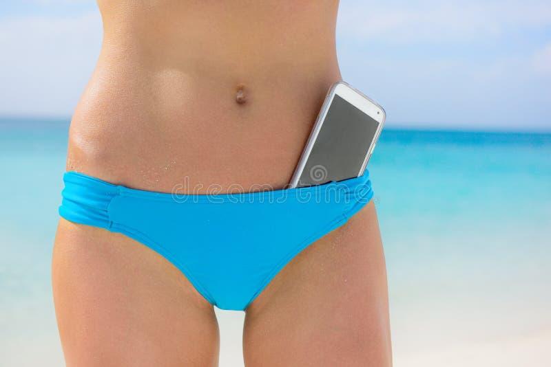 De bikinibodem van de strandvrouw - smartphoneapp concept royalty-vrije stock fotografie