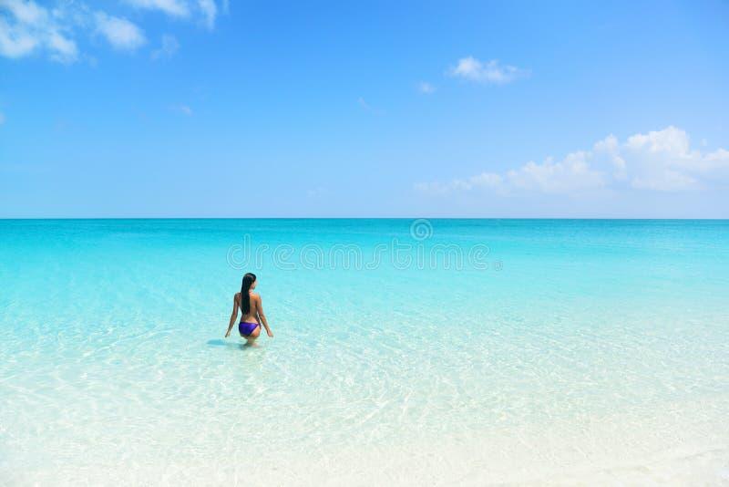 De bikinivrouw die van de strandvakantie in blauwe oceaan zwemmen stock foto