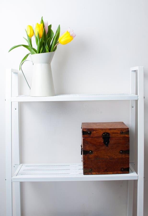 De binnenhuisarchitectuur van het huis: een boeket van tulpen en een doos stock afbeelding