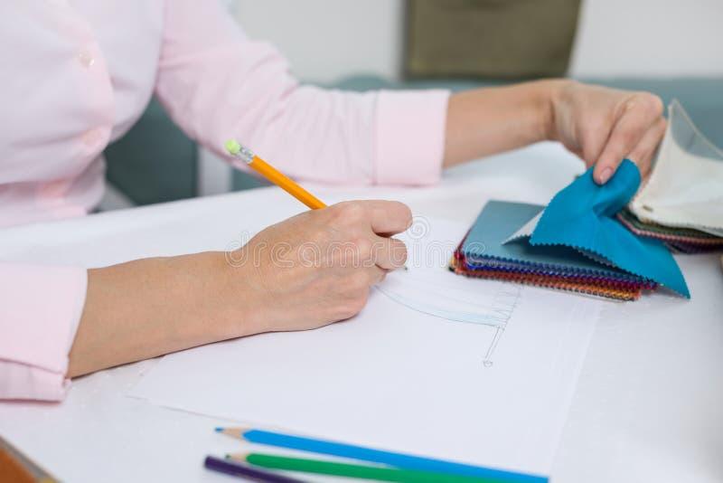 De binnenlandse ontwerper trekt bij bureau in bureau met potlood stock foto