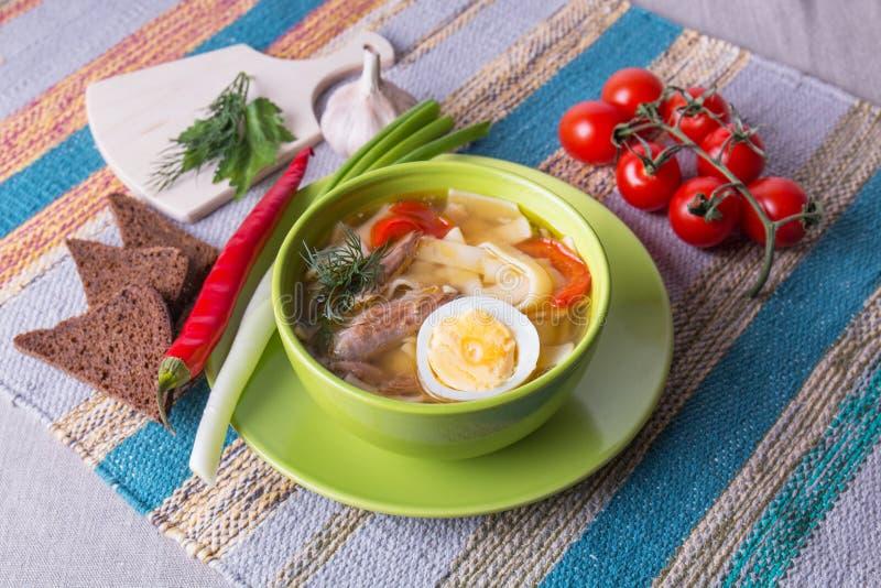De binnenlandse soep van de kippennoedel met verse groenten en ei stock afbeeldingen
