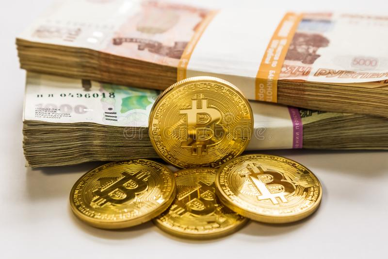 Or de Bitcoin et le rouble russe Pièce de monnaie de Bitcoin sur le fond des roubles russes photo libre de droits