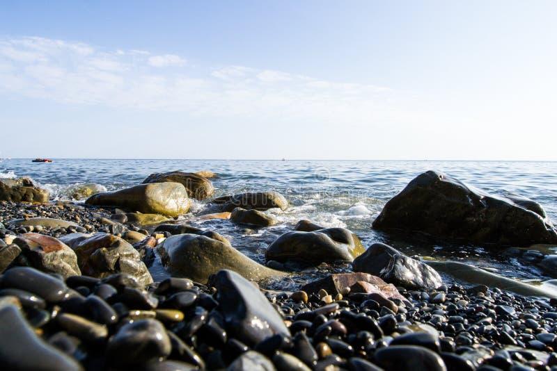 De blåa vågorna som kraschar mot stenarna som ligger på kusten av Blacket Sea royaltyfria bilder