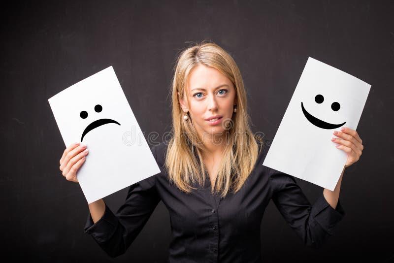 De bladen van de vrouwenholding met droevige en gelukkige smileys royalty-vrije stock foto