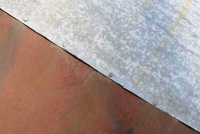 De bladen van roestig rood en geschat zilveren staal worden samen vastgenageld royalty-vrije stock foto's