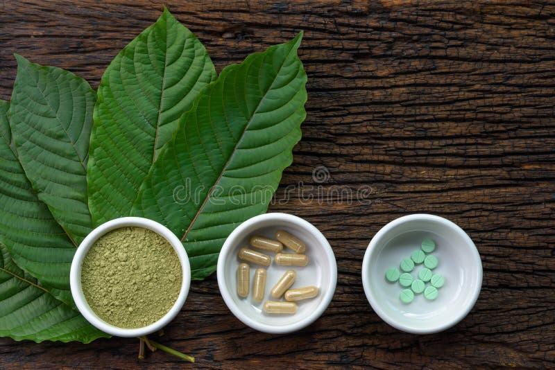 De bladeren van Mitragynaspeciosa kratom met geneeskundeproducten in poeder, capsules en tablet in witte ceramische kom met houte stock foto
