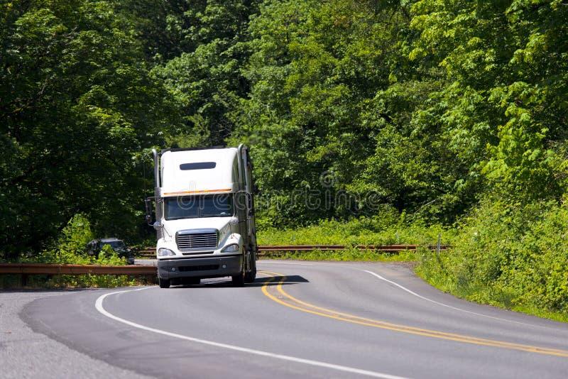 De blanc camion semi enroulant la route verte photos libres de droits