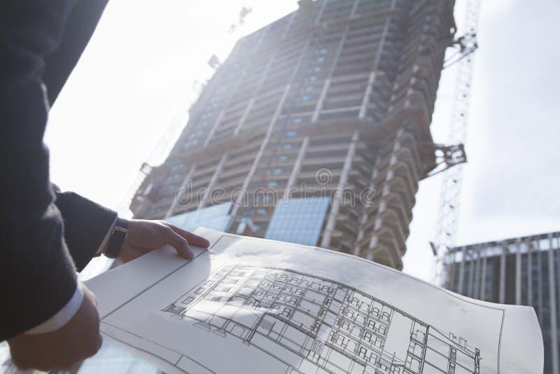 De blauwdruk van de architectenholding van de bouw bij een bouwwerf, midsection stock fotografie