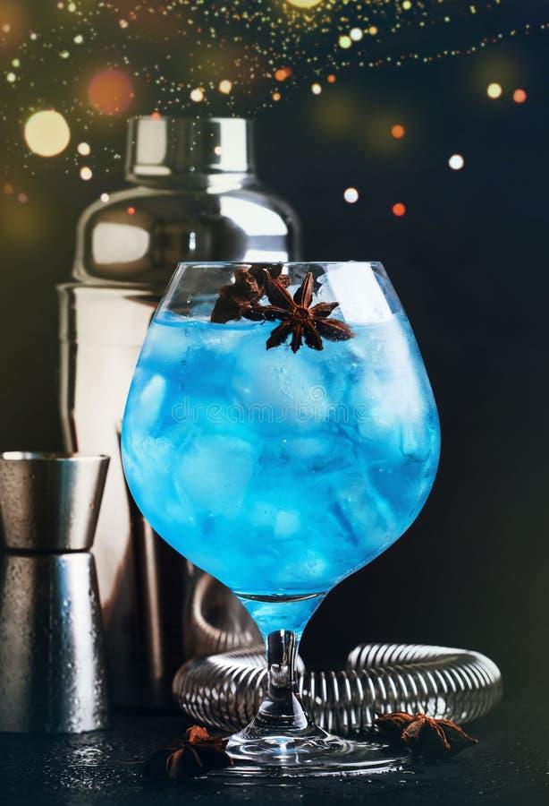 De blauwe alcoholische cocktail met sambuca, likeur, citroensap, verpletterde ijs en anijsplantsterren in groot wijnglas met barm royalty-vrije stock fotografie