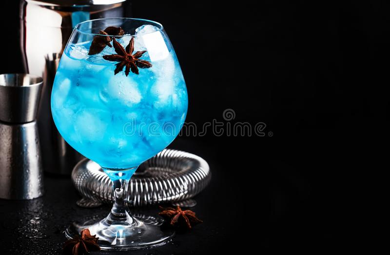 De blauwe alcoholische cocktail met sambuca, likeur, citroensap, verpletterde ijs en anijsplantsterren in groot wijnglas met barm stock fotografie