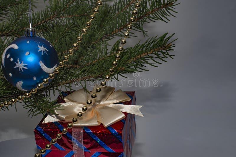 De blauwe bal naast de Kerstboom en de grijze achtergrond stock afbeelding