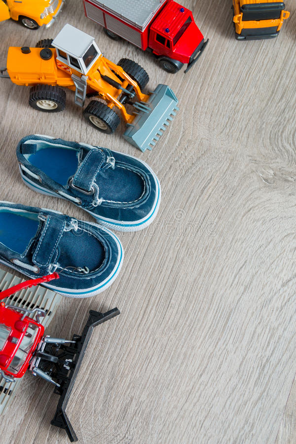 De blauwe bootschoenen voor jongen plaatsen dichtbij van autostuk speelgoed op grijze houten achtergrond Hoogste mening Kader De  royalty-vrije stock foto