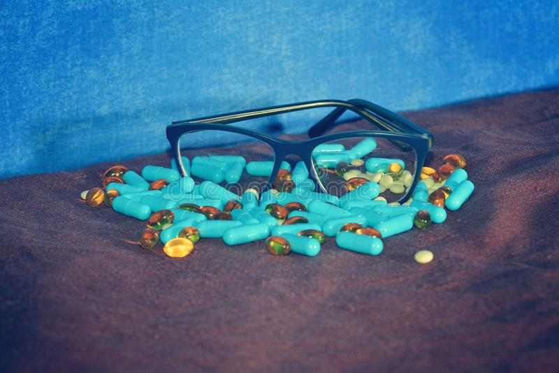 De blauwe capsules en de verschillende pillen zijn verspreid op de bruine oppervlakte van rowades met glazen op een blauwe achter royalty-vrije stock foto's