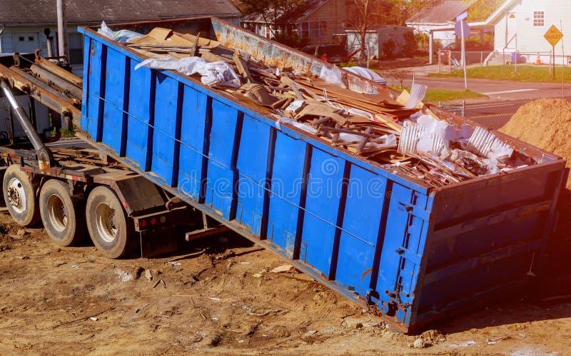 De blauwe die container van het bouwpuin met rots en concreet puin wordt gevuld Industriële huisvuilbak stock foto's