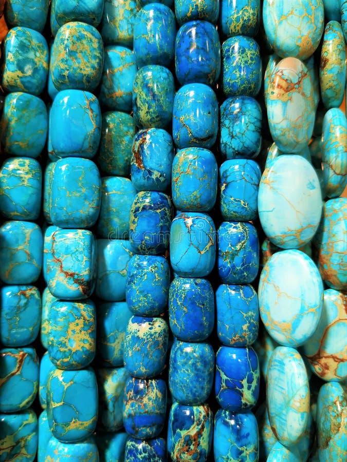 De blauwe en blauwe parels met stroken van wit hangen op de muur Parels van verschillende vormen Gemaakt van natuurlijke en halfe stock afbeeldingen